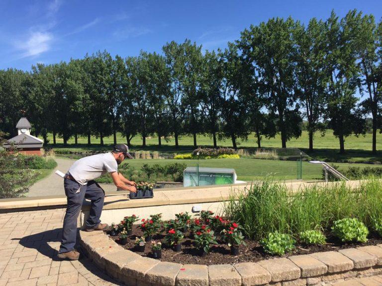 Travailleur plantant des fleurs dans un aménagement paysager