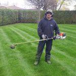 Ouvrier sur une pelouse avec un coupe-herbes