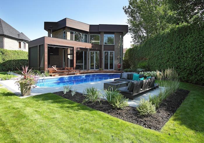 Arrière de maison en bois avec piscine et fauteuils extérieurs