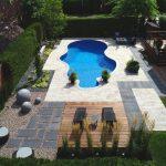 Cour arrière avec piscine creusée, espace foyer et chaises longues