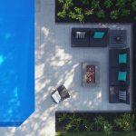 Espace foyer sur du pavé à côté d'une piscine, vu à vol d'oiseau