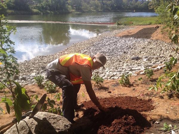 Ouvrier travaillant la terre sur des berges