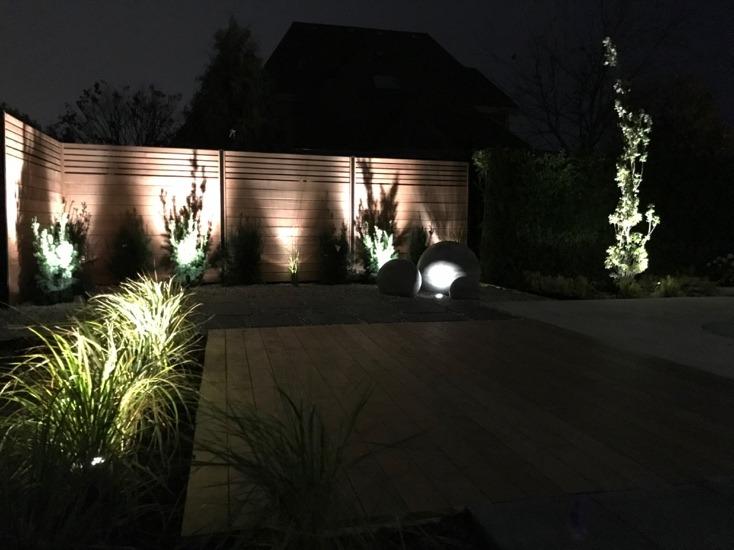 Lampes éclairant une clôture et l'aménagement paysager de nuit