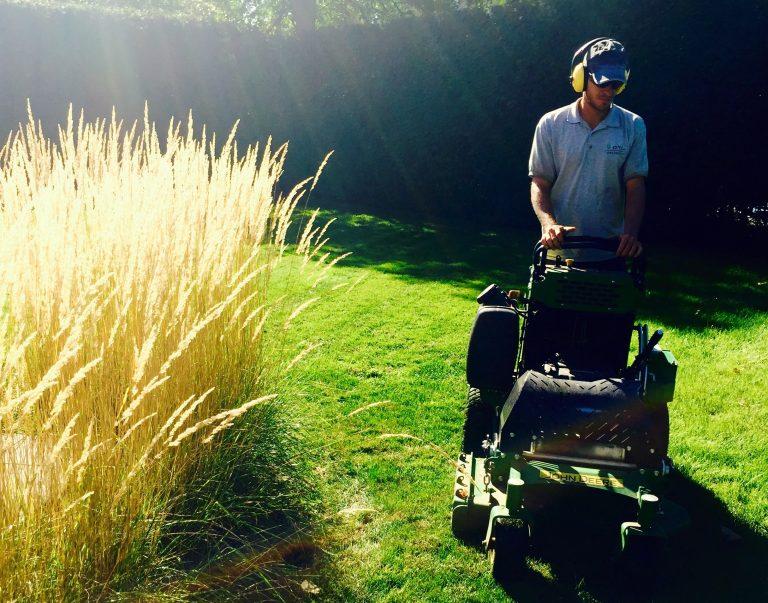 Ouvrier passant une tondeuse sur la pelouse