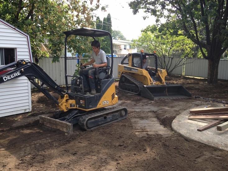 Ouvrier manoeuvrant un tracteur lors d'une excavation de cour arrière