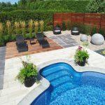 Chaises longues à côté d'une piscine creusée avec plates-bandes