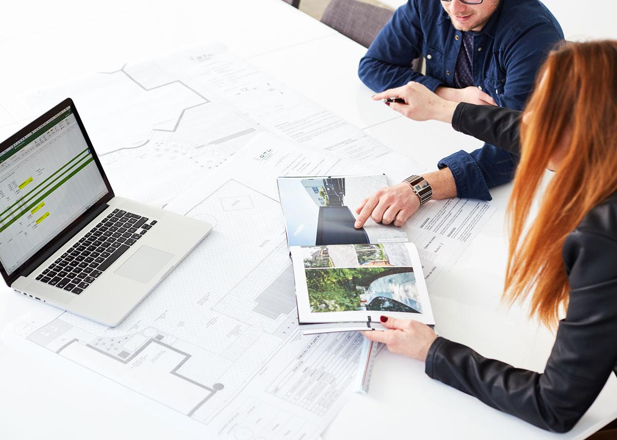 Architectes de paysage en réunion avec ordinateur et plans