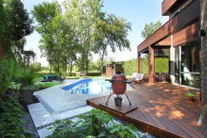 Terrasse arrière en bois avec piscine et pavé