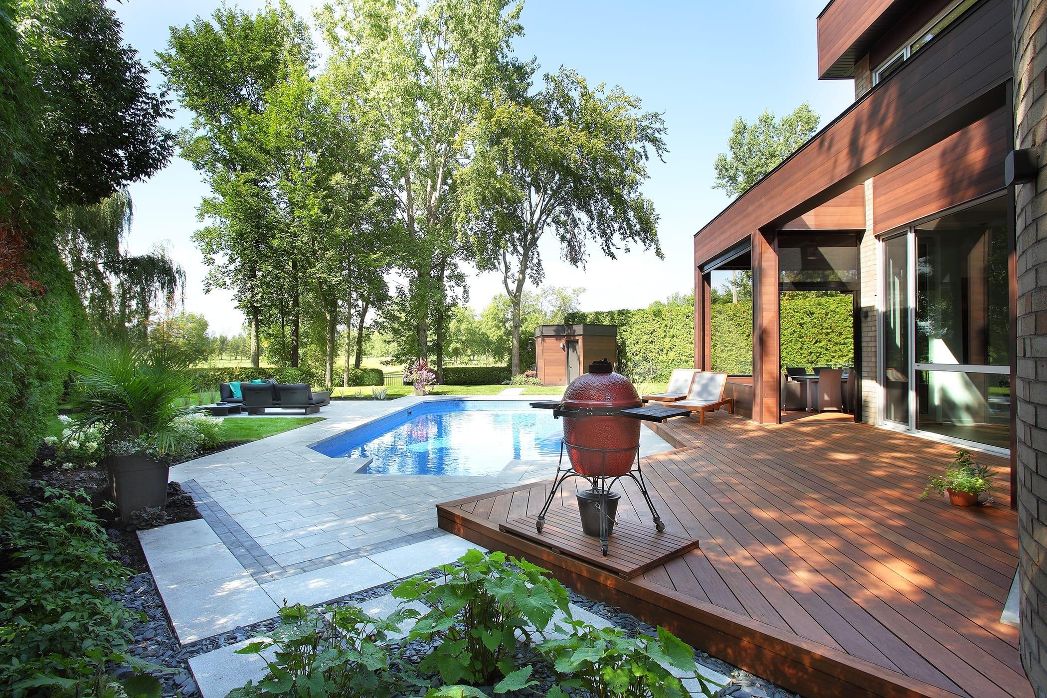 Arrière de maison avec deck en bois et piscine