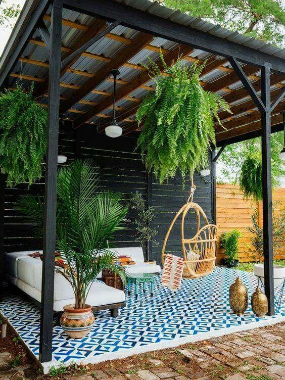 Salon extérieur sous une pergola avec plantes suspendues