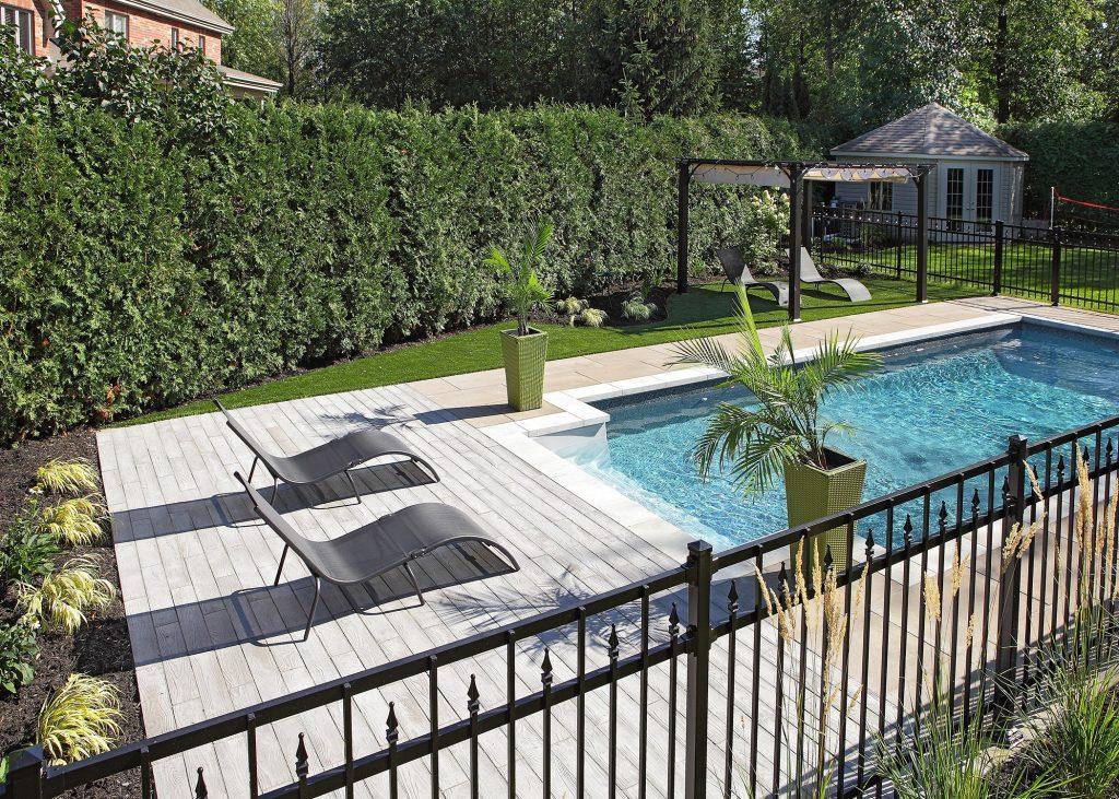 Cour arrière clôturée avec piscine et chaises longues