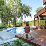 Terrasse arrière en bois avec piscine, pavé et barbecue