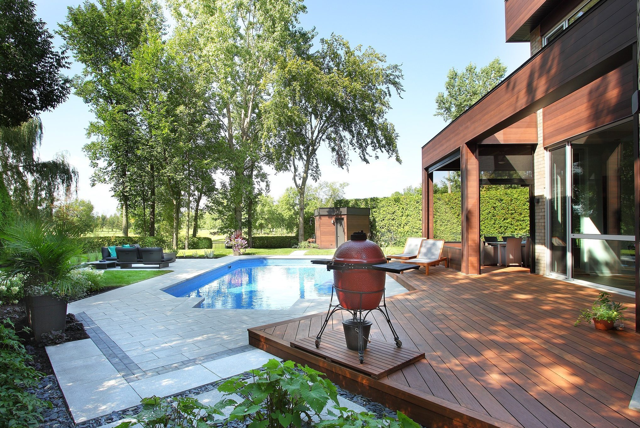 Aménagement paysager avec piscine à l'arrière d'une maison