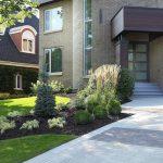 Aménagement paysager à l'avant d'une maison, avec plates-bandes de graminées et conifères