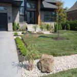 Aménagement paysager et entrée de garage à l'avant d'une maison
