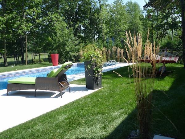 Aménagement paysager d'une cour arrière avec piscine, chaise longue et plantes en pots