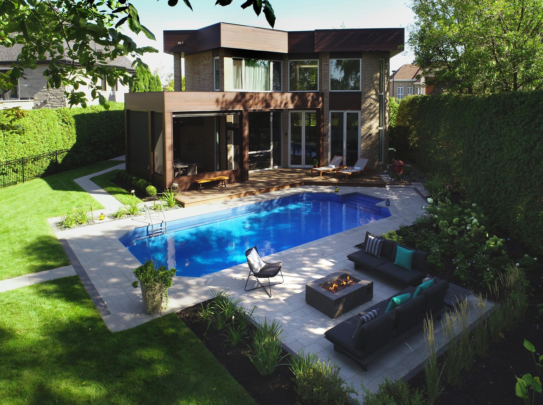 Aménagement paysager arrière, avec piscine, foyer et divans extérieurs