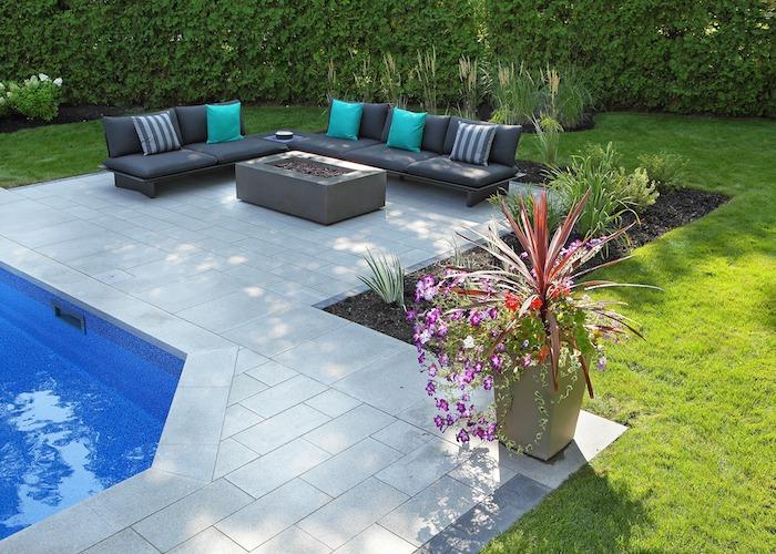 Aménagement paysager d'une cour avec fleurs en pot et espace foyer