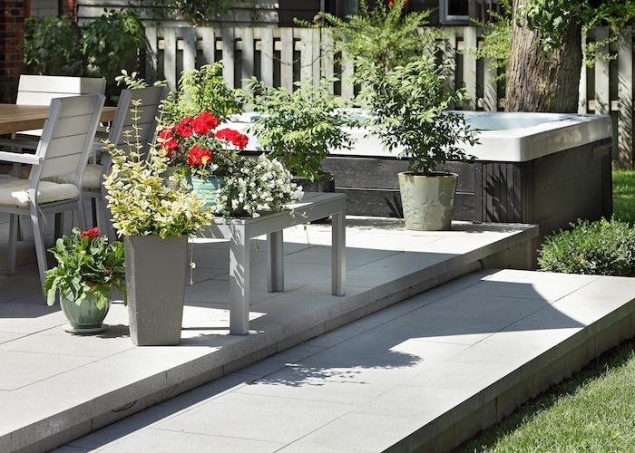 Terrasse en pavé avec fleurs et plantes en pots, attenante à un spa