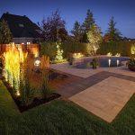 Aménagement paysager de nuit avec piscine, chaises longues et éclairage paysager