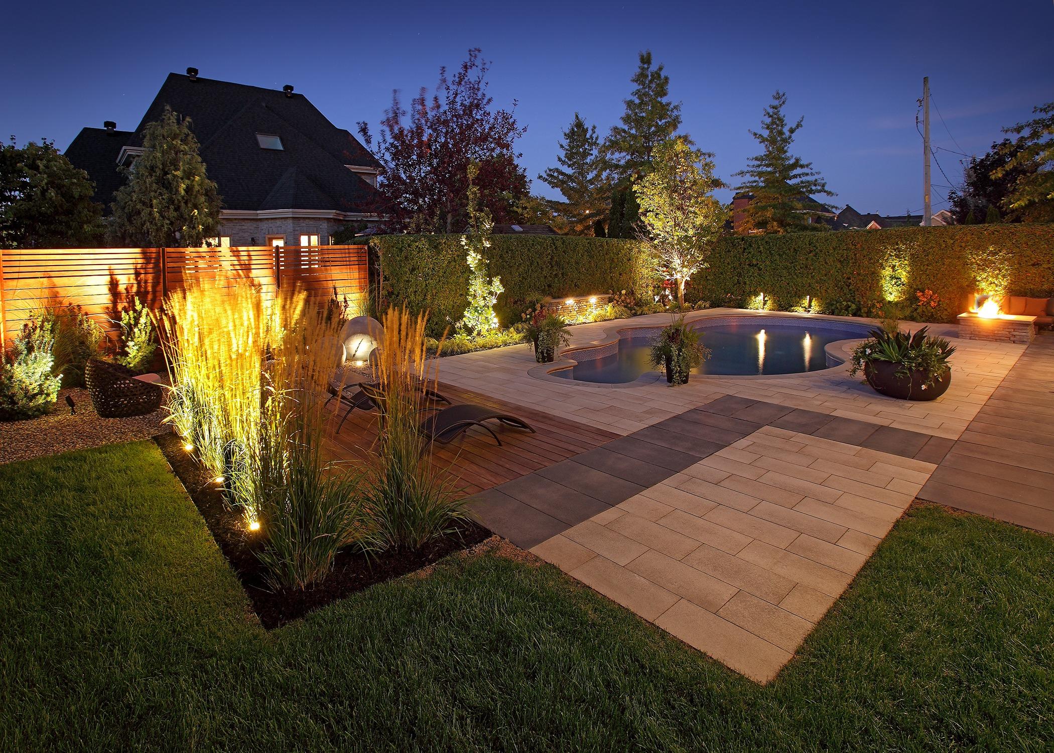 Aménagement paysager avec pisicne, chaises longues et plantes ornementales