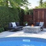 Foyer de pierres devant un cabanon de bois et au bord d'une piscine