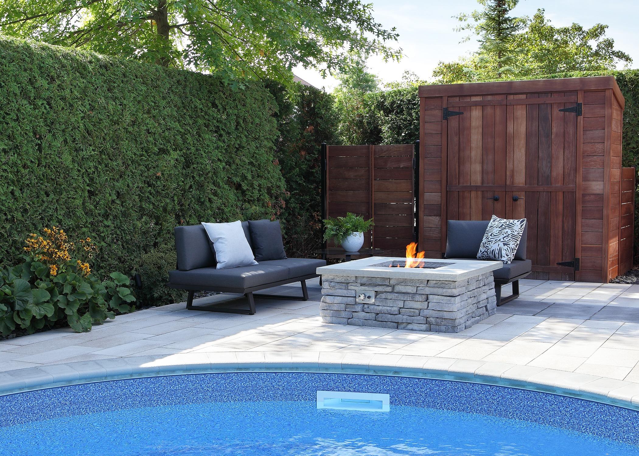 Espace foyer au bord d'une piscine avec cabanon de bois