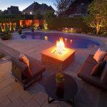 Coin foyer au bord d'une piscine de nuit avec éclairage paysager