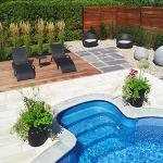 Chaises longues au bord d'une piscine creusée avec pots de fleurs