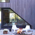 Coin foyer extérieur avec chaises blanches au bord d'une maison