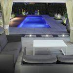 Espace détente extérieur de nuit avec piscine éclairée