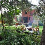 Espace foyer avec chaises Adirondack entouré de plantes