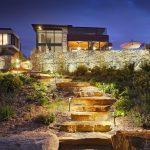 Aménagement paysager d'une maison avec un terrain en pente qui donne sur le fleuve avec mur de gabion