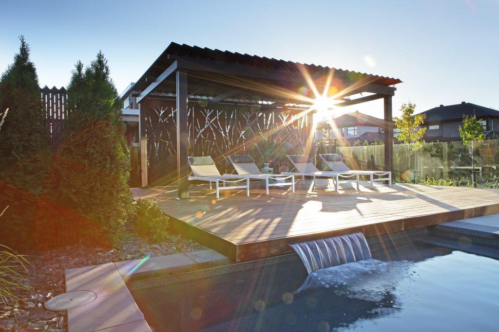 Pergola dans un jardin prêt d'une piscine avec chaises longues